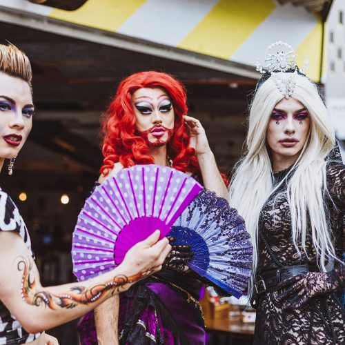 Three drag queens posing on the street
