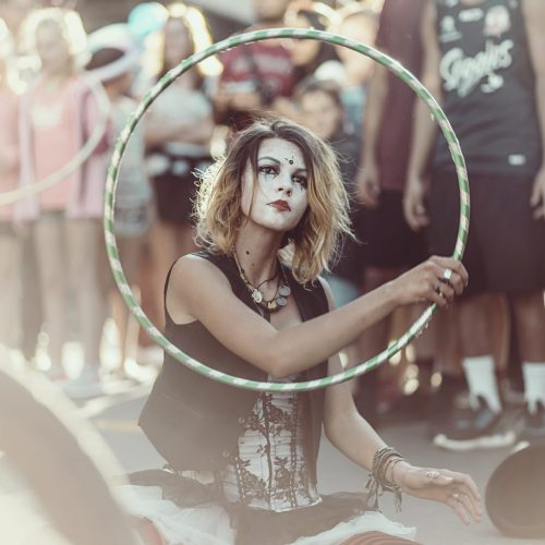 Street performer with white face paint sitting on the street doing an act with a hoola hoop