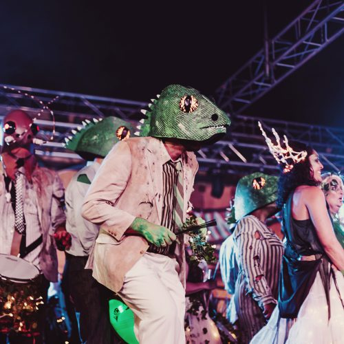 Batucada group performing in lizard costumes on stage at night