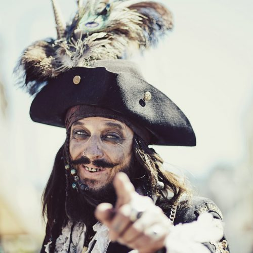 Close up of a man dressed as a pirate grinning and pointing at the camera